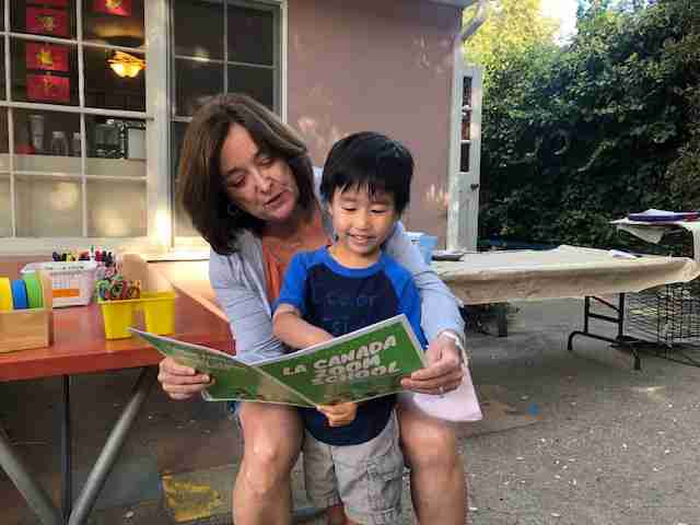 little boy and miss debbie reading a zoom school book