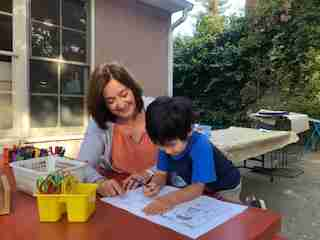 teacher with small child working on zoom school workbook